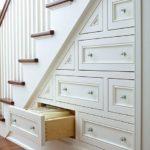 Белые выдвижыне шкафчики под лестницей