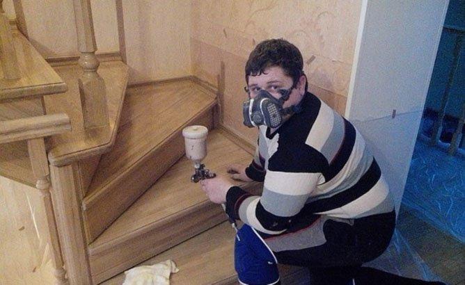 Мужчина в респираторе окрашивает лестницу из краскопульта